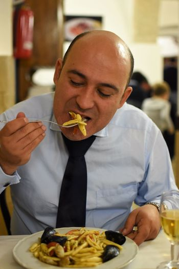 Close-Up Of Man Eating Food In Restaurant