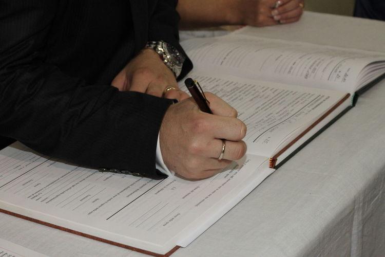 Bridegroom writing on book