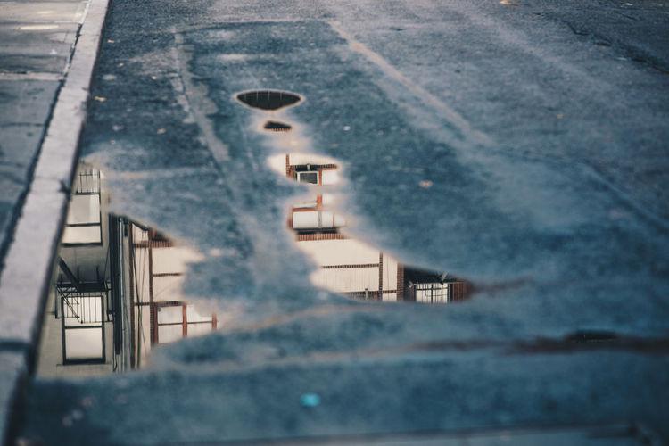 Tilt image of car on street against sky during winter