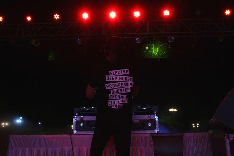 Rear view of dj playing music in nightclub