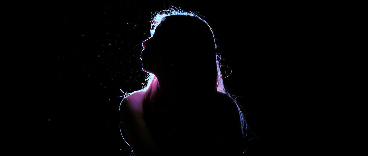 PORTRAIT OF SILHOUETTE WOMAN AGAINST ILLUMINATED LIGHTS