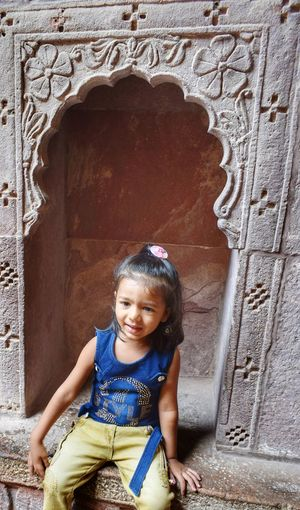 Child Portrait Childhood Sitting Smiling Girls Looking At Camera Happiness Full Length Front View Place Of Worship Elephant Religion Spirituality Arch Cathedral Temple Temple - Building Christianity Mosque Church