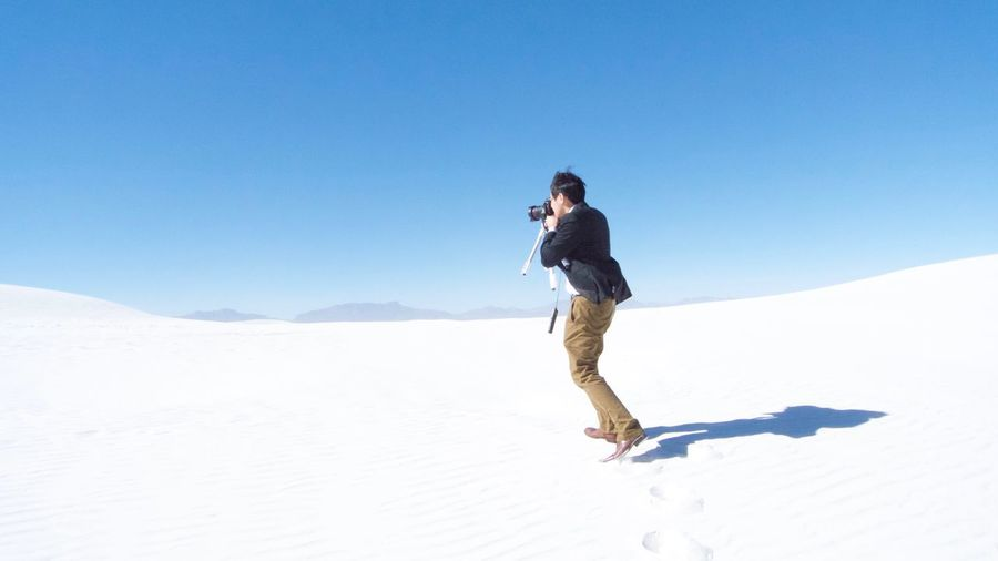 Full length of man photographing against clear sky
