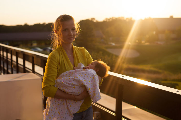 Portrait of woman holding baby girl while standing by railing against sky during sunset
