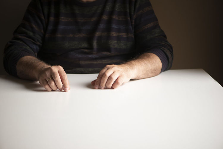 Midsection of man sitting on table