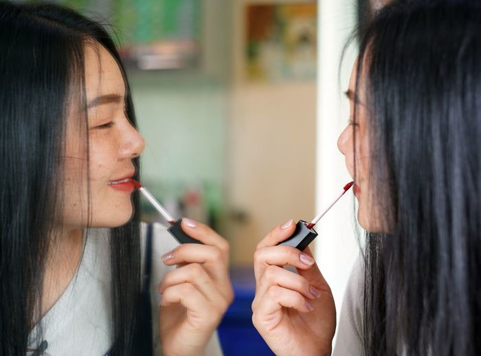 Close-up of woman applying lipstick while looking at mirror