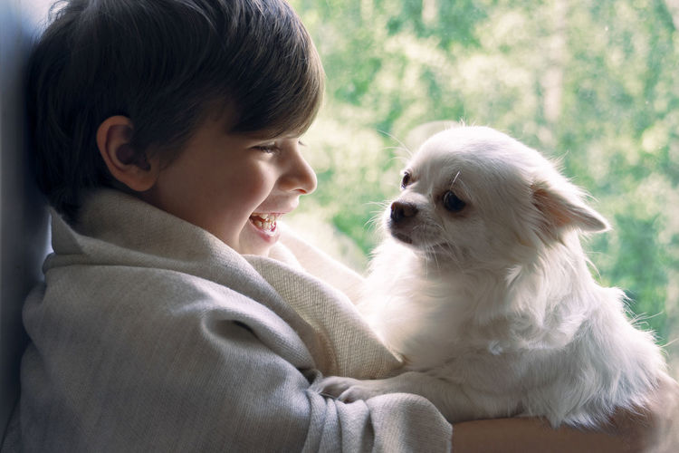 Rear view of boy with dog looking away
