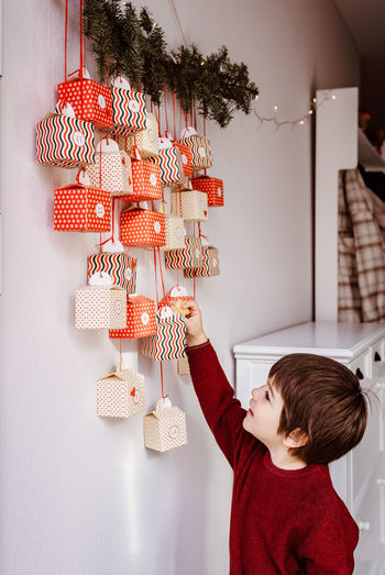 Full length of a girl holding christmas tree in box