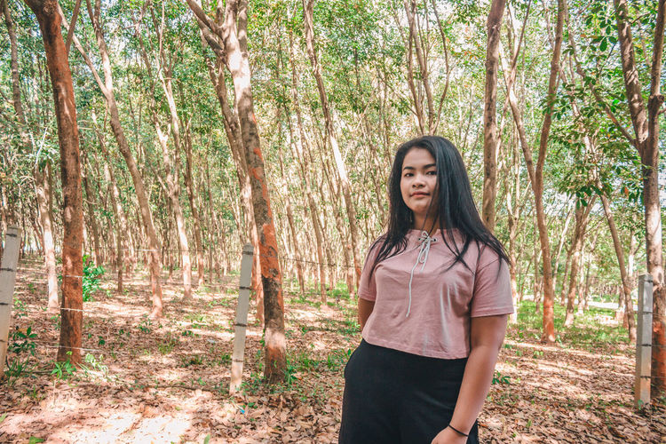 Portrait of young woman with long hair standing against trees in forest