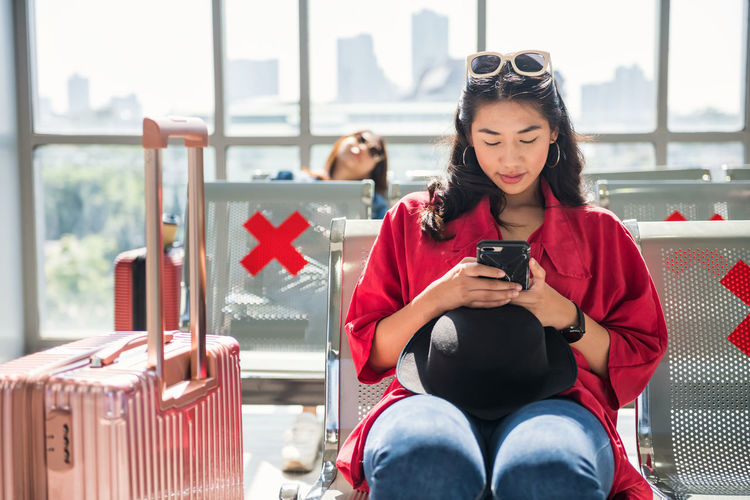 Young woman using mobile phone while sitting at airport