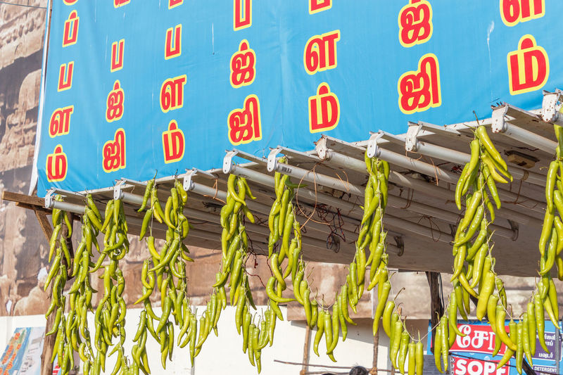 Local food stall selling chilly pakodas and green chilies are made to hang like a chain Business Chily Sale Alphabet Close-up Communication Day Food Hanging In A Row Large Group Of Objects No People Outdoors Pakoda Stall Text