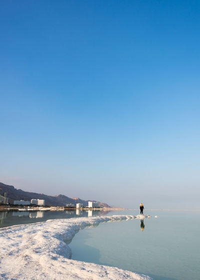 Man on beach against clear sky during winter