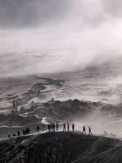 People on mountain against cloudy sky