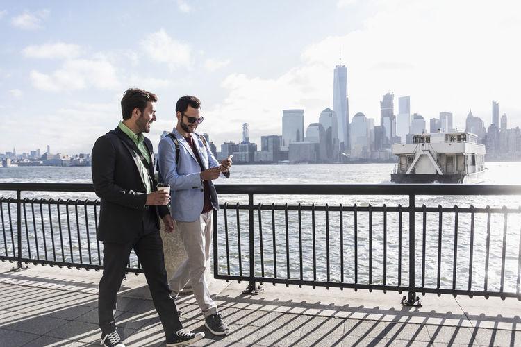 Men standing on railing against cityscape