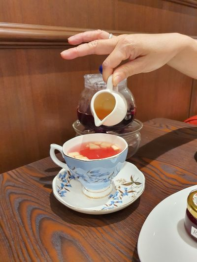 Midsection of woman holding tea cup on table