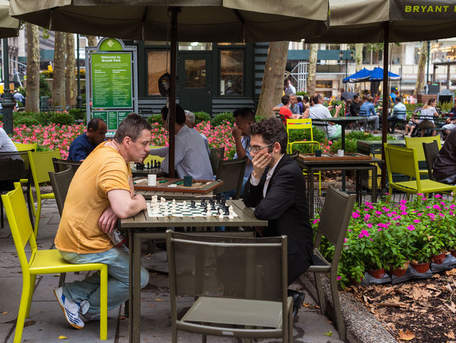 Two men play chess in Bryant Park in Midtown Manhattan Bryant Park NYC Chessboard Man Manhattan Chess Flowers Game Leisure Activity Outdoors, Outside, Open-air, Air, Fresh, Fresh Air, Park Table And Chairs