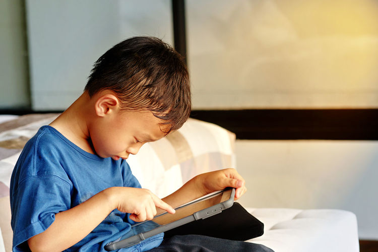 Side view of boy using digital tablet at home