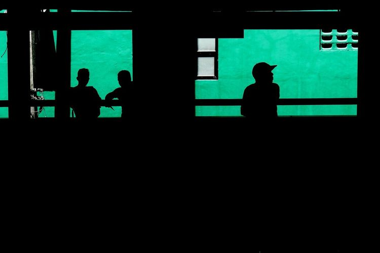 Silhouette People Against Green Wall