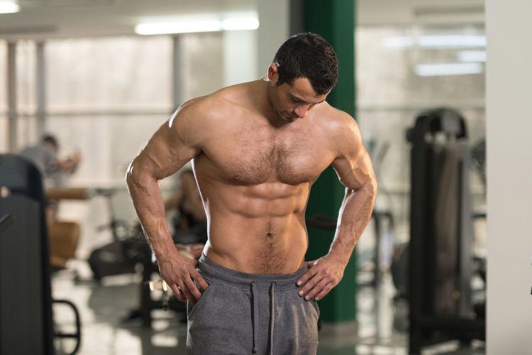 Shirtless man standing in gym
