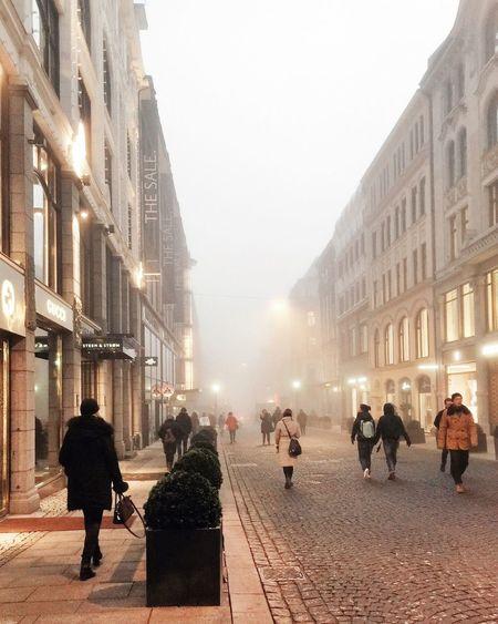 People on street in city against sky