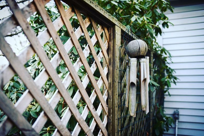 Wooden Wind Chime Hanging On Fence At Yard