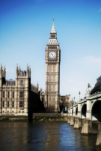 Big ben by thames river against clear sky in city