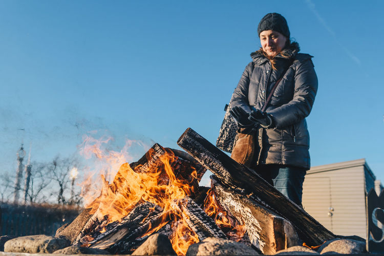 Woman warming herself by fire Cold Weather Burning Casual Clothing Clear Sky Cold Temperature Day Flame Front View Full Length Heat - Temperature Leisure Activity Lifestyles Nature One Person Outdoors People Real People Sky Snow Standing Warm Clothing Winter Wood - Material Young Adult Young Women Fresh On Market 2018