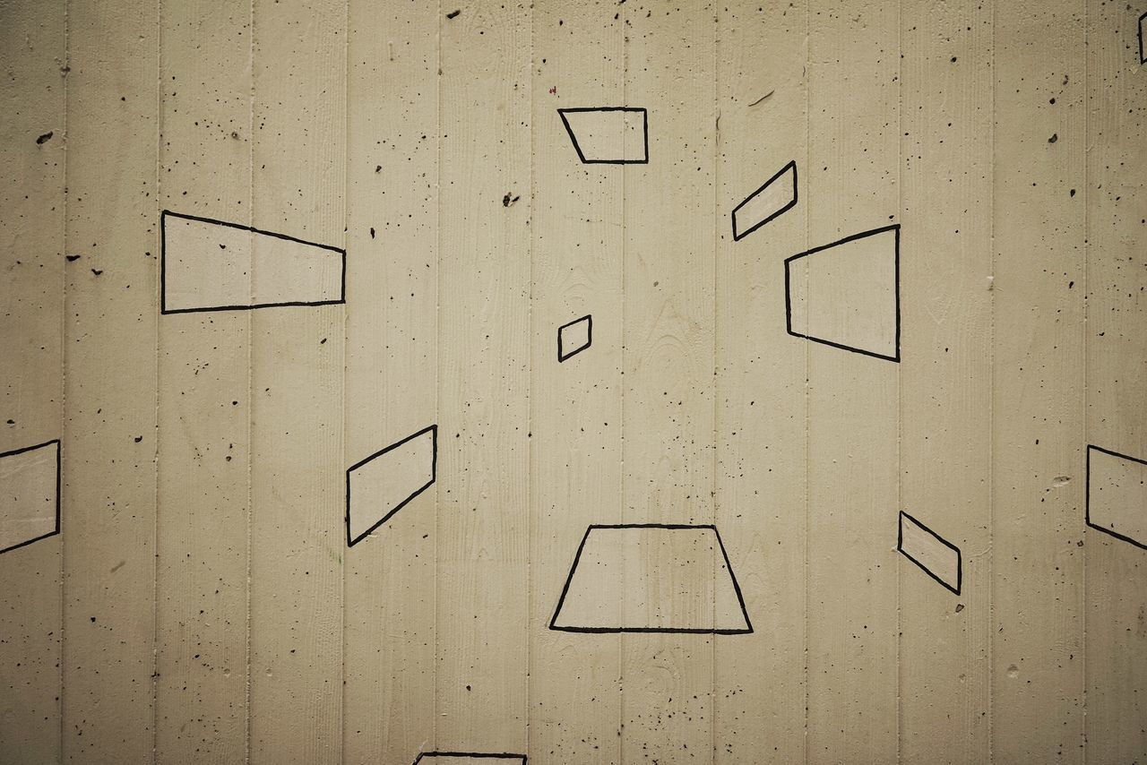Close-Up Of Geometric Shape Drawings On Wooden Wall