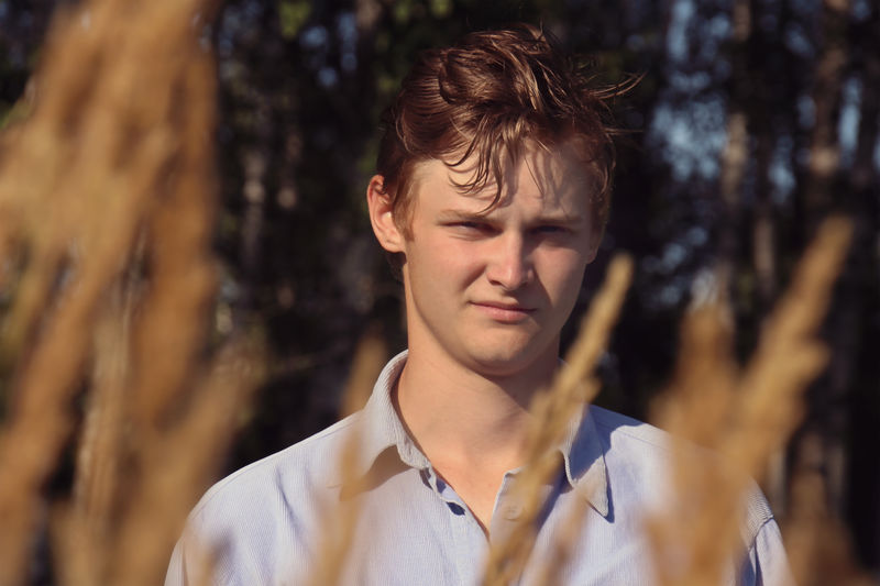 Portrait of young man seen through plants