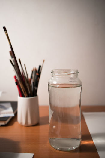 Brushes on a wooden desk Brushes Glass Jar Studio Creativity Image Light Paint Set Close-up Creativity Has No Limits Design Desk Organizer Indoors  No People Paintbrush Table Tools Wooden
