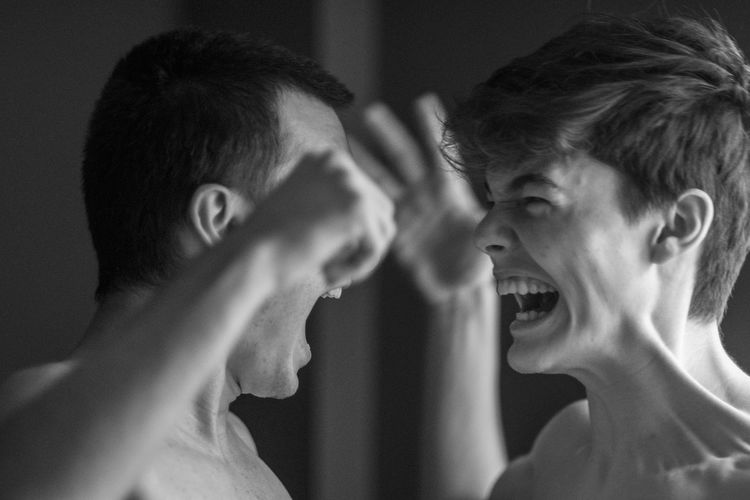 Close-up of young man and boy fighting at home