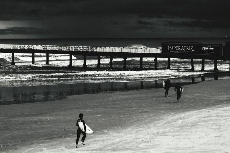 Boy walking on pier at beach