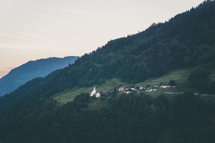 A small Swiss town on top of a green hill Alps Beauty In Nature Blue Hour Disentis Dorf Dusk Graubünden Green Village Hill Hill Town Idyllic Landscape Little Village Lovely Mountain Mountain Village Nature Outdoors Schweiz Suisse  Sunset Switzerland Town View Village