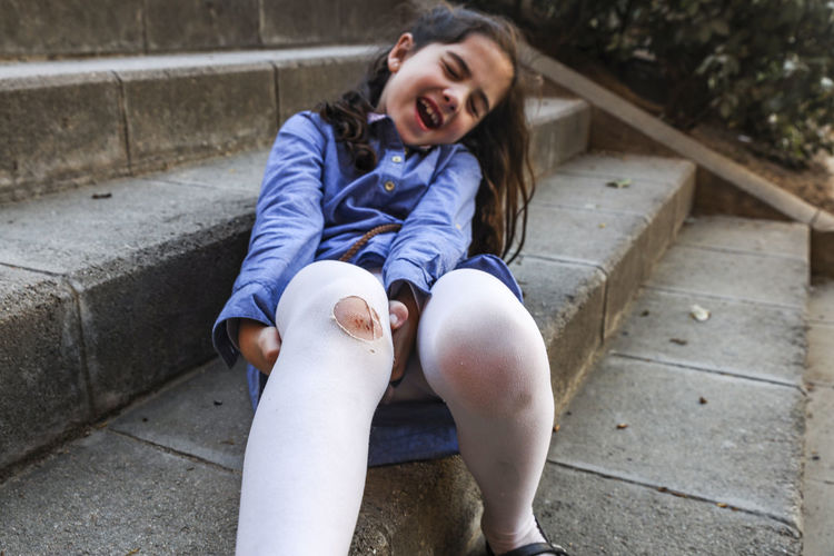 Knee Wound Crying Hurt Blood Leg Childhood Child One Person Emotion Real People Girls Full Length Staircase Sitting Women Lifestyles Front View Innocence Females Day Portrait Happiness Steps And Staircases Mouth Open