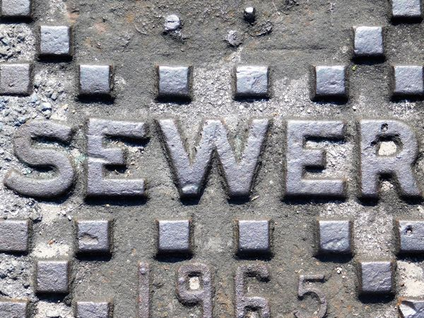 Backgrounds Beauty In Everything Communication Full Frame Gray Metal No People Notes From The Underground On The Road Outdoors Pattern Pieces Pattern, Texture, Shape And Form Patterns & Textures Random Acts Of Photography Road Sewer Sewercover Squares Street Streetphotography Text Texture Textured  Textures And Surfaces Western Script
