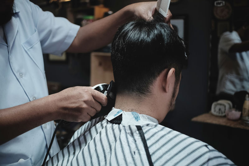 Midsection of barber cutting hair of customer at shop