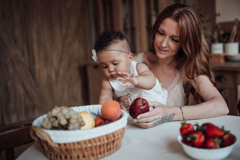 Mother and daughter against fruits