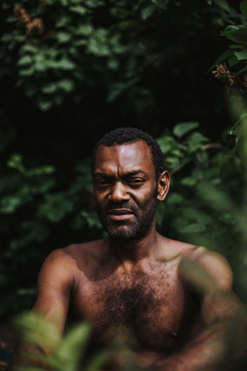 Portrait of shirtless man sitting against plants