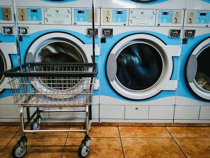 Shopping cart against washing machine at laundromat