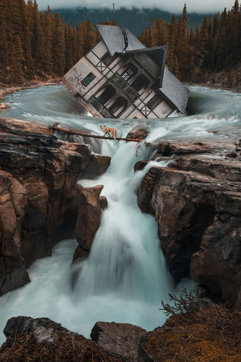 Scenic view of waterfall with house drowning in background