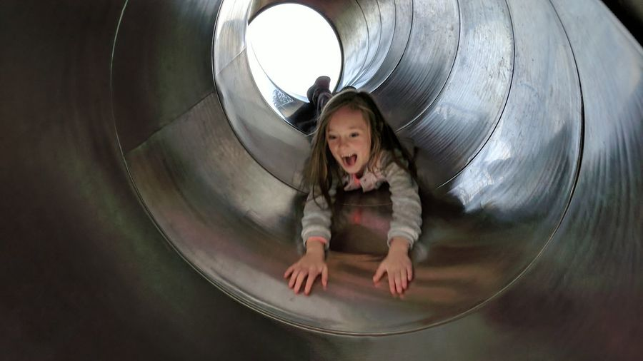 Cheerful girl sliding in tunnel slide at playground