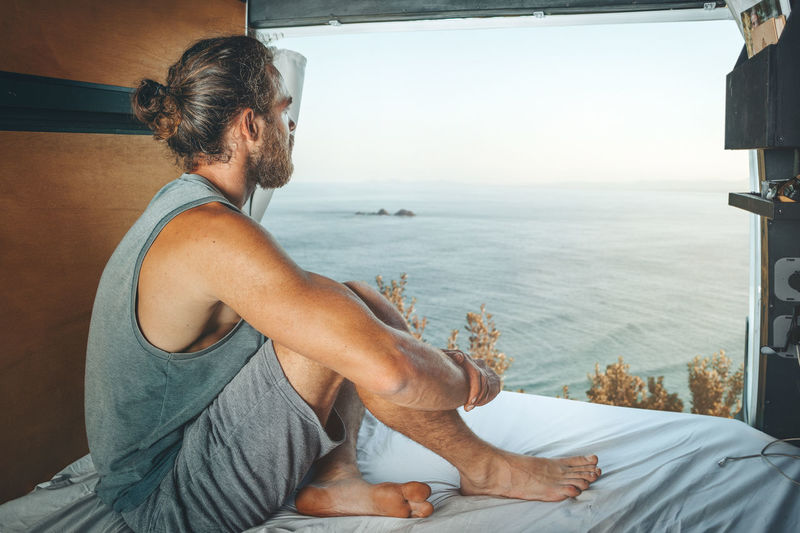 Rear view of man sitting on bed against sea