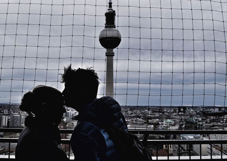 Man Kissing Girlfriend On Forehead By Fernsehturm In City