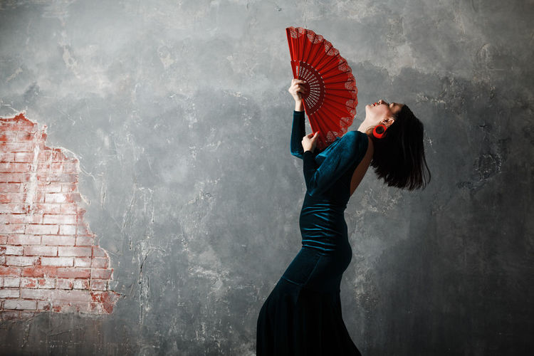 Side view of woman holding hand fan against wall