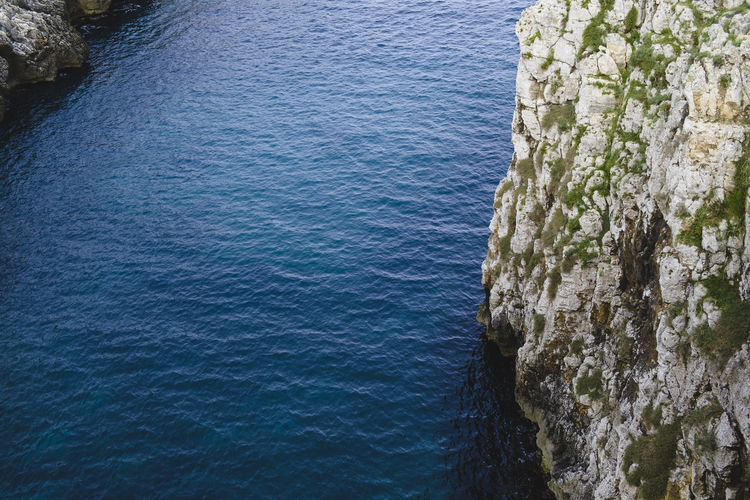 High angle view of rocky cliff by sea
