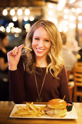 Burger Fries Close-up Eating Food Food And Drink Freshness Front View Happiness Indoors  Leisure Activity Long Hair Looking At Camera Night One Person Plate Portrait Ready-to-eat Restaurant Sitting Smiling Table Unhealthy Eating Women Young Women