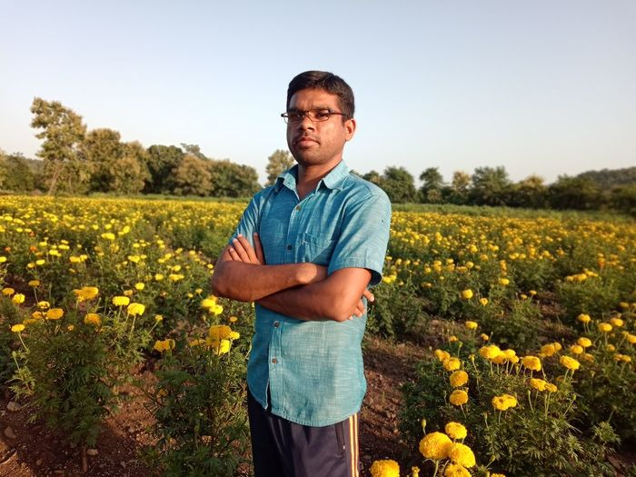 Man standing on marigold field