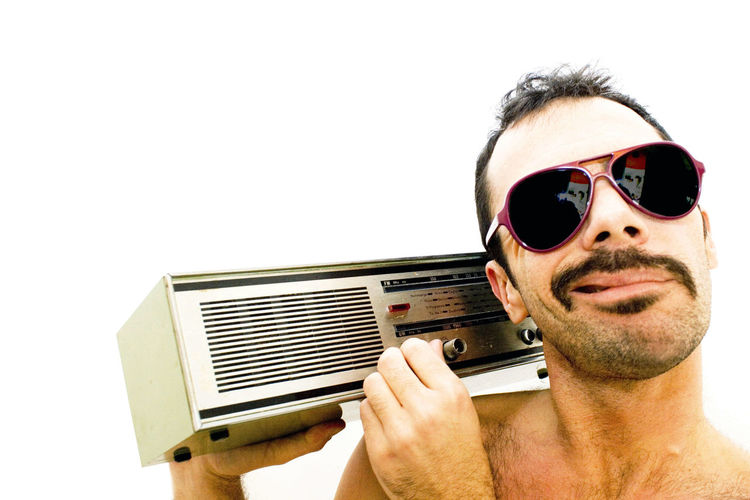 Portrait of man wearing sunglasses while holding radio against white background