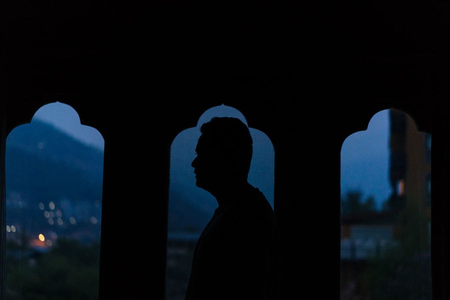 Man looking out of the window early morning. Arch Architecture Building Exterior Built Structure Copy Space Focus On Foreground History Leisure Activity Lifestyles Men Nature Night One Person Outdoors Real People Silhouette Sky Standing The Past