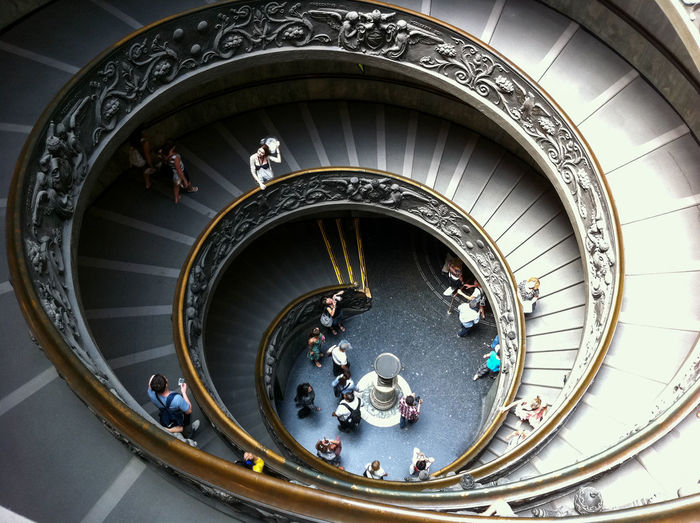 High angle view of people walking on spiral stairs